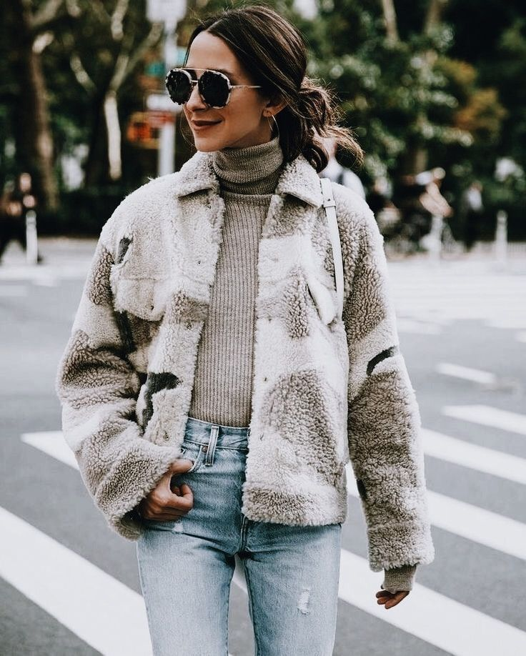 Cute cozy jacket over beige turtleneck and blue jeans.