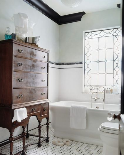 Classy, traditional bathroom by Panageries features a leaded glass window and an antique dresser for storage. The black and white tile are also traditional, but play beautifully against the modern tub. Note also how the crown molding does not go all around the room - neat!