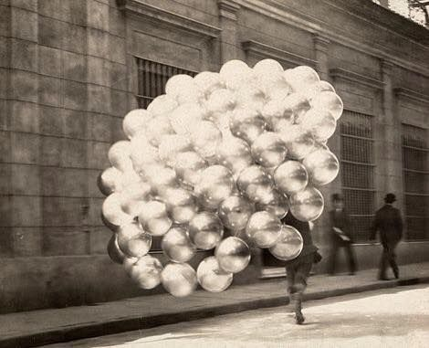 A balloon vendor runs across a road with a trailing mass of balloons in Buenos Aires, November 1921. Photograph by Newton W. Gulick, National Geographic.