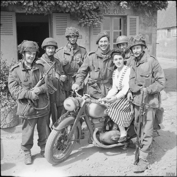 British glider troops pose with a local French girl on a captured German motorcycle in Normandy following Operation Deadstick, an attack by airborne forces of the British Army to capture intact two road bridges across the River Orne and the Caen Canal providing the only exit eastwards, for British forces from their landing on Sword Beach (June 15, 1944). The man on the left is armed with a German MP38, and the soldier wearing the beret has already captured a P.38 pistol and done his best to…