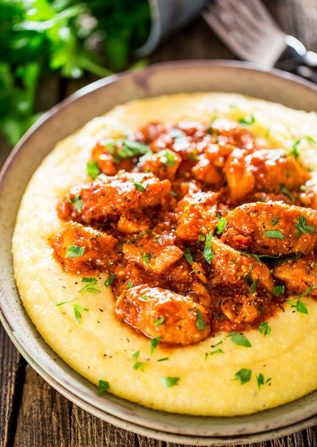 Saucy Chicken and Sausage over Creamy Parmesan Polenta - a true comfort meal if there ever was one. Delicious chicken and sausage in a spicy tomato sauce served over a creamy and cheesy polenta.