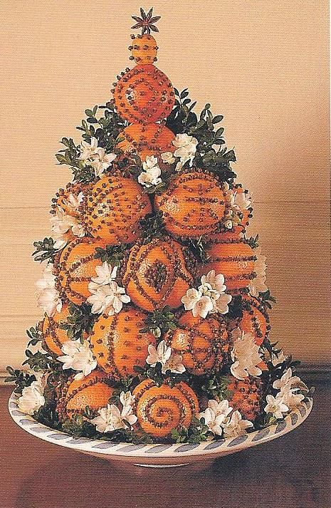 A dramatic cone designed with  clove-studded naval oranges  topped with a kumquat  is not only beautiful but smells wonderful!  Narcissus blooms are tucked in between along with boxwood as fillers.  LOVE this!  :)