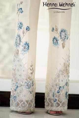Ivory raw silk boot cut trousers with teal diamante embroidery and embellishment with tassel accessories. Please note these are trousers only. Please note deli
