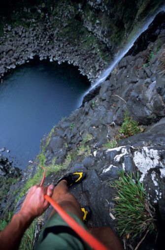 Stock Photo : A canyoning guide looks down the 500 foot rappel of the Takamaka Gorge, Reunion Island, France.