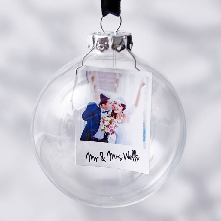 A beautiful Mr And Mrs Personalised Christmas Bauble. Display your favourite memories together. Each bauble features your own photograph printed as a miniture polaroid.Please place your order by using the option menu to the right hand side of this produt listing. Once your order has been placed please attach the images which you require to have included in the baubles. If you have any questions please do get in touch, we'd love to help! Please Note: Personalisation will be identical to…
