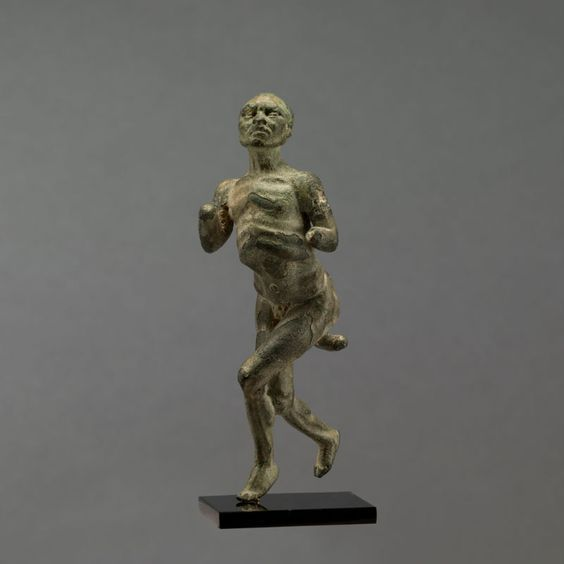 Hellenistic bronze statuette of a dancer, 2nd century B.C. The man of an astonishing thinness is a hunchback and has a large deformity on his chest, which is of large circumference, maybe in his youth he was a victim of rickets, his enormous phallus has gotten caught between his legs. The age of the dancer is difficult to estimate but the sooth forehead and the features of the face seem to indicate that he is a man of some age, 7.8 cm high. Private collection