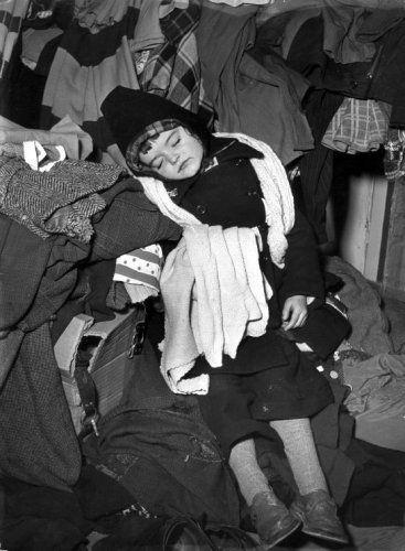 Slapend meisje tussen kleding, slachtoffer van de watersnoodramp in Zeeland, februari 1953.