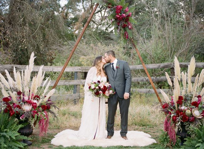Boho wedding ceremony site with a wooden arch + berry florals