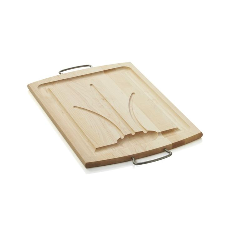 Crafted of North American maple, this classic carving board features artful, sloped channeling on the carving side so that juices trickle down into the deep well, where they can be recovered for au jus or added to gravy.  With a smooth side on the reserves and stainless steel handles, this handsome board transitions to the table for slicing and presentation of foods.