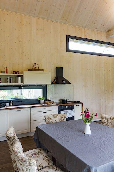 Dřevěnému obložení zdí v interiéru přirozeně sekundují dřevěné pracovní plochy v kuchyni i kuchyňská linka v krémové barvě.