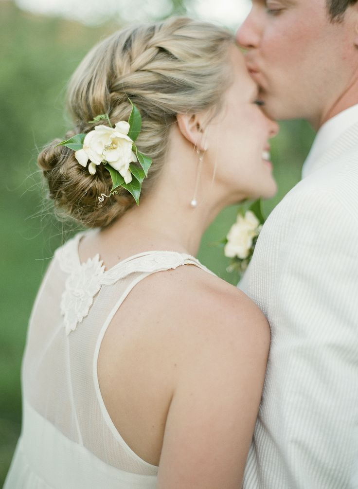 Trança lateral finalizada com um coque baixo enfeitado com flores. #penteado #noivas