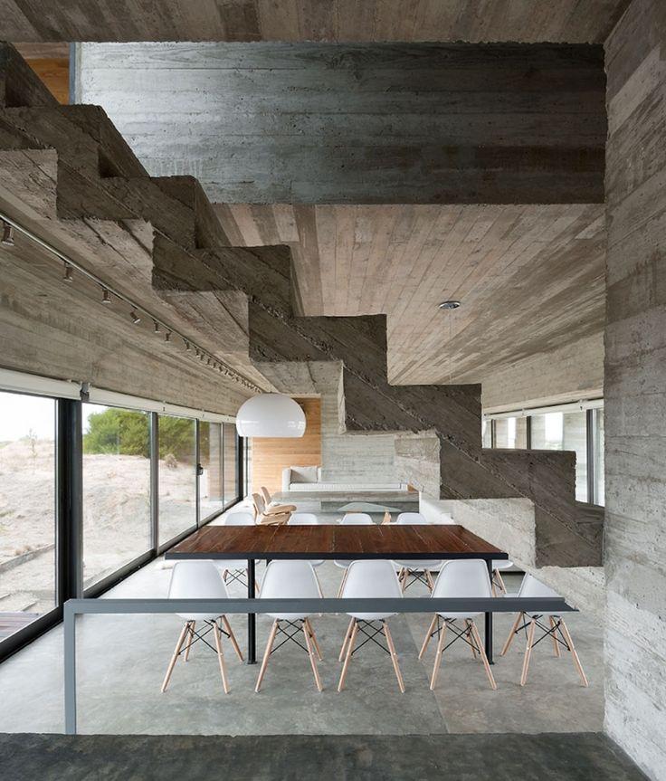 sol en béton ciré, escalier droit, table à manger en bois massif et chaises assorties