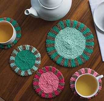 "Knitting Pattern for Promenade Coasters and Trivet - Inspired by Depression-era patchwork quilts, these coasters and trivets are worked back and forth in rows and seamed, with short-rows used to created the striped edging. Coasters: 5"" diameter. Trivet: 7½"" diameter."