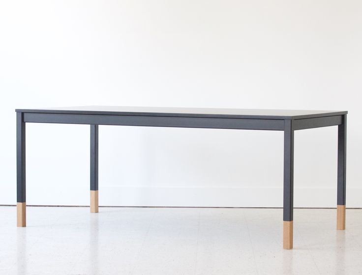 Black on black modern table with oak leg inserts. Commonly used as a kitchen table, dining table and workplace table. Doodle Table by KROFT.