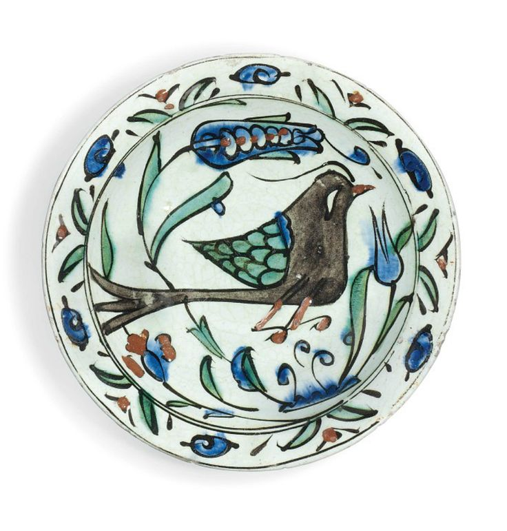 AN INTACT FIGURAL IZNIK POTTERY DISH OTTOMAN TURKEY, MID-17TH CENTURY On short ring foot, with sloping rimg, the decoration on white ground with a bird amidst foliage, the borders with stylized floral decoration, the foot drilled and chipped, otherwise intact 9½in. (24cm.) diam.