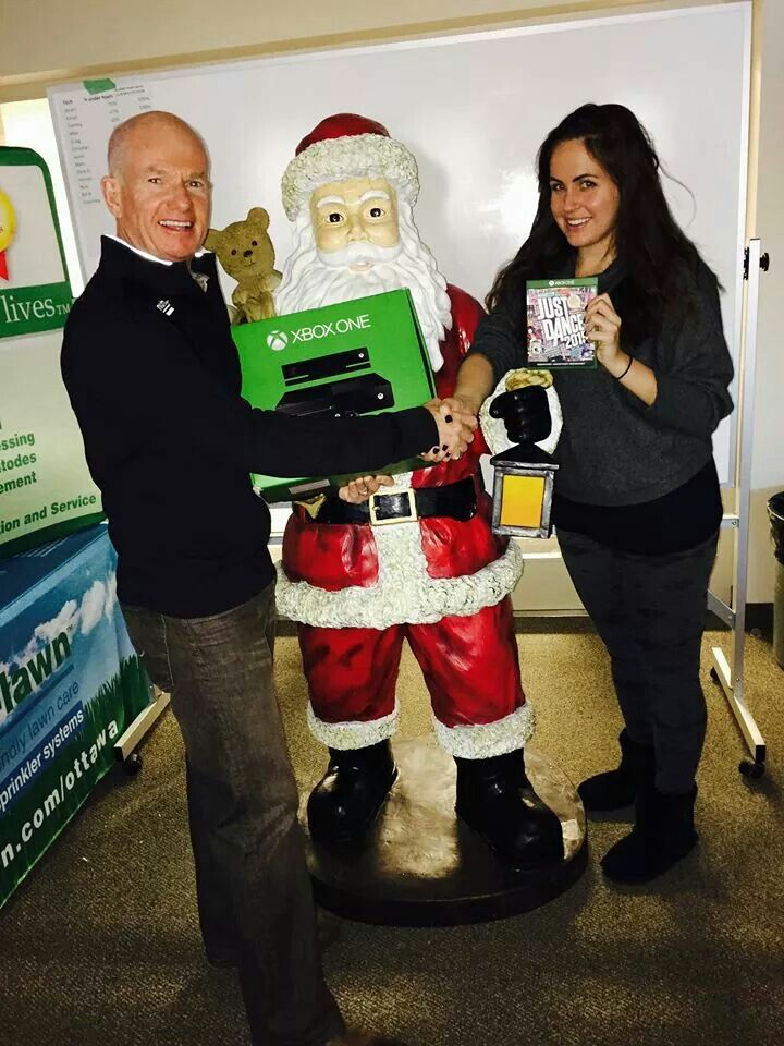 Thom Bourne presenting Samantha with an XBox for winning the dance competition at the 2014 Nutri Lawn Christmas Party!