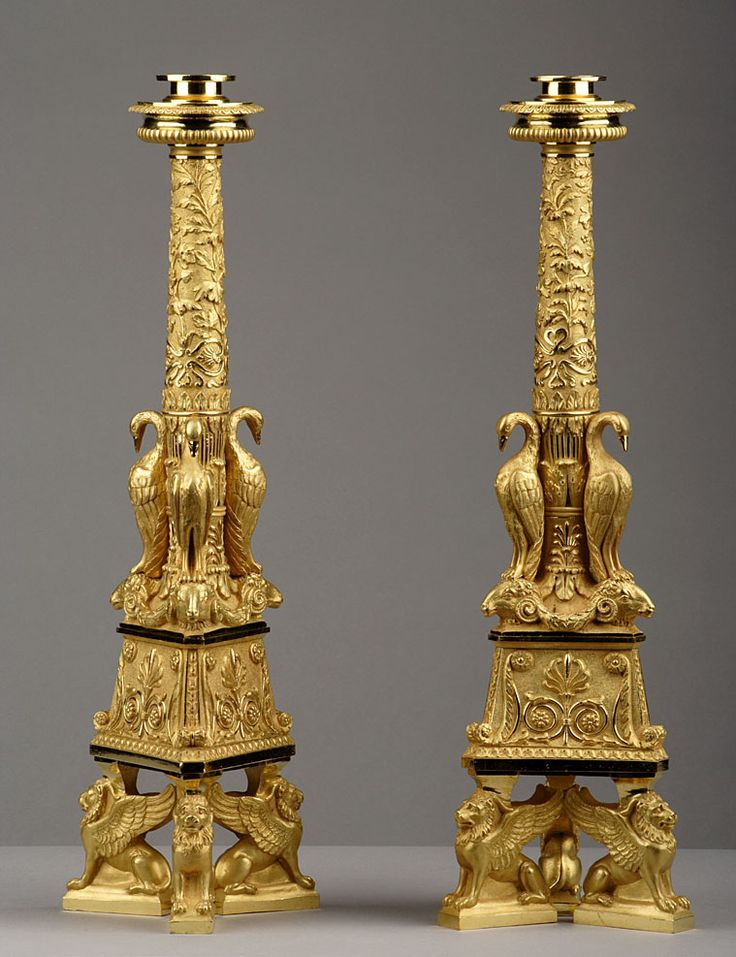 A pair of large candlesticks in gilt bronze, resting on a tripod base with…