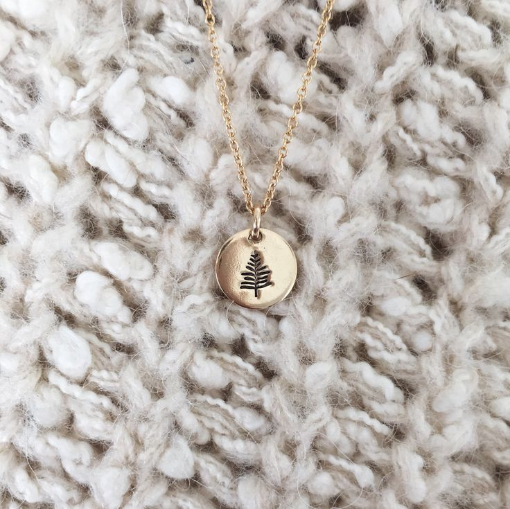 "A simple reminder to stay grounded and remain true to your roots. The Evergreen is stamped on a 3/8"" disc. Goes great with other necklaces for a beautiful layered look. - Necklace chain comes in 16"","