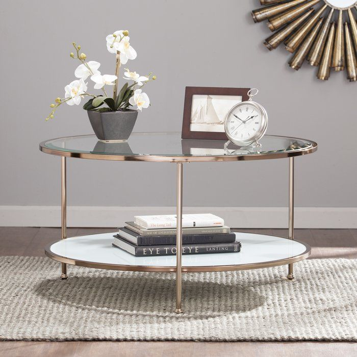 Luxe looks and a streamlined frame make this chic coffee table a living room must-have. Made from stainless steel in a rose gold-hued finish, this dazzling design includes three tubular posts and two round gleaming glass shelves. For a glamourous ensemble in the living room, start by rolling out a bright shag area rug to define the space, then arrange a button-tufted chesterfield sofa and velvet-upholstered slipper chair around this dazzling design. Place clear acrylic end tables on each end…
