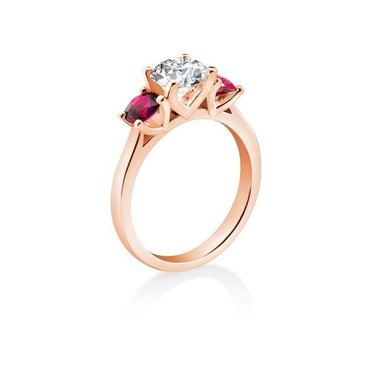 A perfectly matched pair of stunning natural rubies enlivens this classically proportioned 3-stone diamond engagement ring.  Starting From $1299