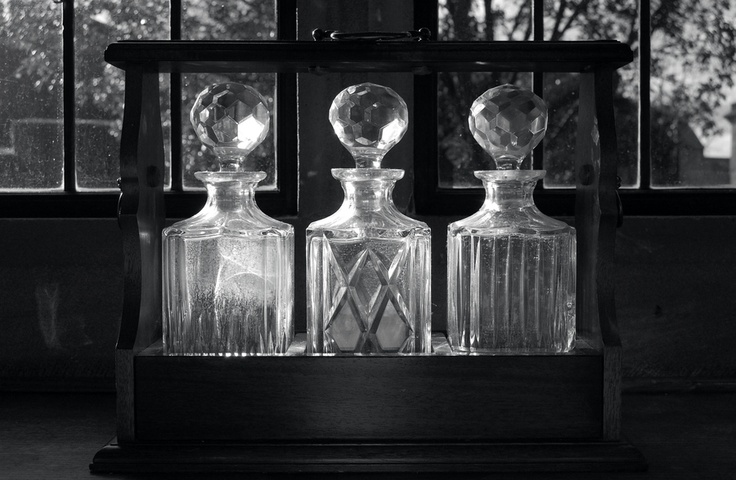 Three crystal decanters photographed in black and white