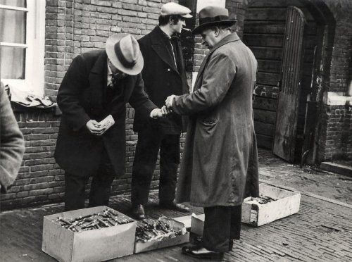 Marktkoopman bij zijn handel, dozen met sigaren, op straat met klant. Nederland, Amsterdam, 1933.