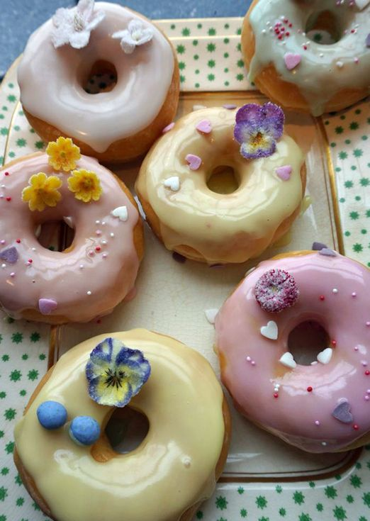 Pastel iced doughnuts decorated with edible crystallised primroses, cowslips and violas for a spring wedding treat