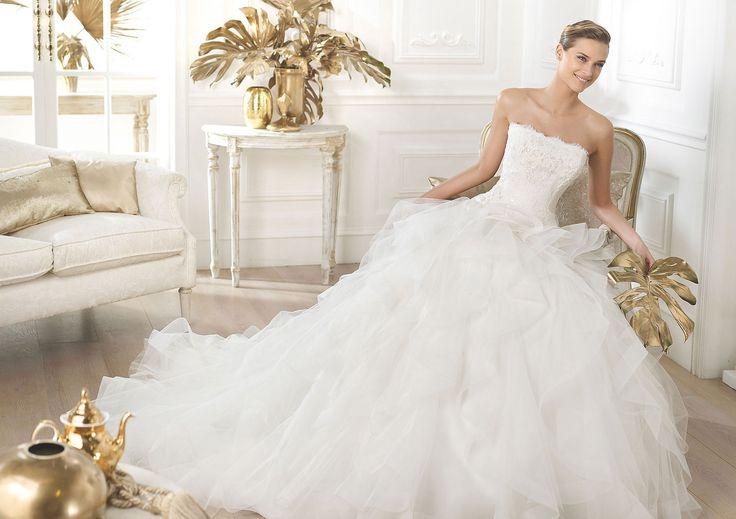 Vestido de novia palabra de honor de encaje chantilly con aplicaciones de encaje rebrodé Y detalles de pedrería nacarada. Falda princesa de volantes de tul con nylon.