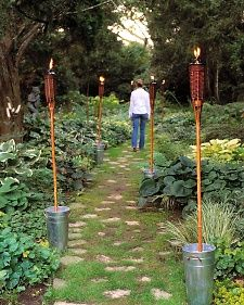 Hold one torch upright in each bucket, and fill the bucket with garden gravel to about 3 inches from the rim. The containers are then heavy enough to support the lit torches