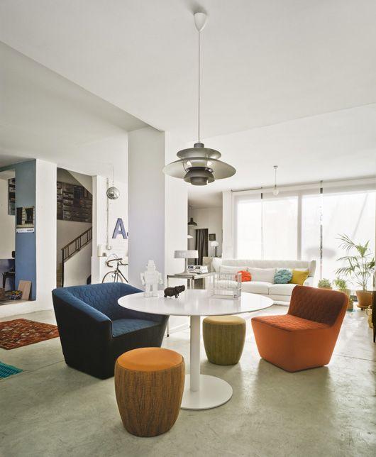 Butacas Tea y pufs Chat alrededor de una Vela-Dora con sofá Folk al fondo. Marca: Sancal
