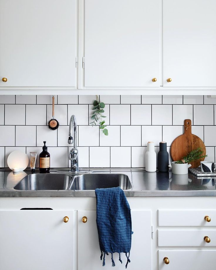 Białe szafki ze złotymi uchwytami w aranżacji kuchni