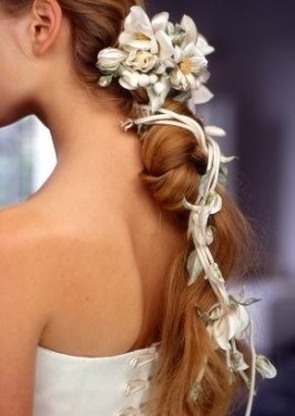 Wedding hairstyle fashionable dark blond long curly hair interspersed with flowers.