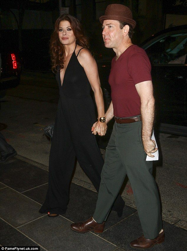 Holding hands: Debra Messing held hands with a mystery man...