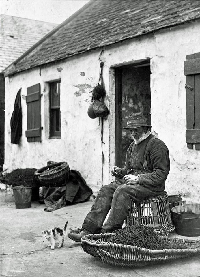 A crofter-fisherman making a net in front of his cottage. Net-making was a long and laborious process, usually undertaken during the winter months. Depending on the size of the mesh, a person could make one or possibly two nets during the course of the winter. https://www.facebook.com/photo.php?fbid=10151743814661172&set=a.10150722242376172.401477.239730476171&type=1&theater K. Ramsay
