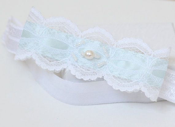 "This bridal garter features a vintage bow, created from a white lace and aqua blue satin ribbon for the traditional something blue"". It is adorned"