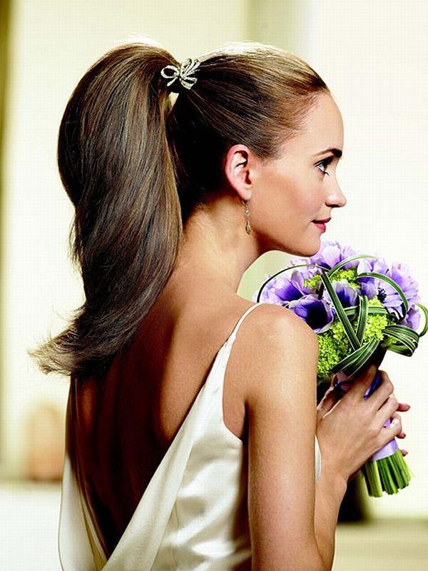 Volume et raffinement sont les maîtres-mots de cette coiffure ! Ici les cheveux sont très tirés en arrière et attachés en une queue de cheval très haute. Un joli bijou en forme de ruban, serti de strass, attache les cheveux. Un accessoire peu ostentatoire mais très chic ! La queue de cheval est ensuite très volumineuse et forme une belle courbe dans le dos de la mariée. Ça, c'est du brushing ! Cette coiffure permet en plus de montrer son joli dos dans le décolleté de la robe.