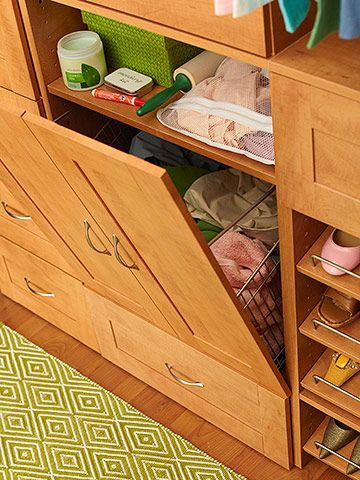 Hidden Laundry Storage  Two joined door panels conceal a tilt-out hamper and mini laundry-prep station. A bag designated for delicate items and laundry essentials is stored on the shelf above for easy grab-and-go access.