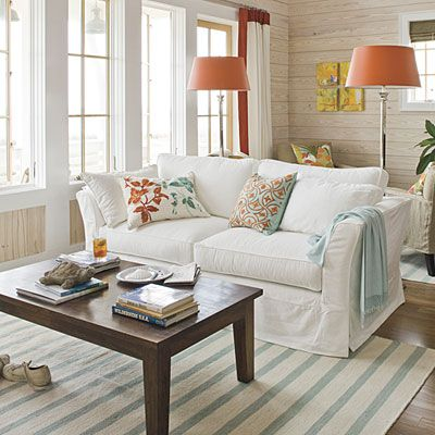 Coastal inspiration; Crisp whites combined with punches of bright colors immediately transport you to the coast. In this living room, aqua accents in the pillows, throw, and rug mimic the ocean's dazzling blues, and the pops of bright orange are inspired by the magnificent hues of the setting sun. Whitewashed horizontal shiplap planking evokes the feel of old Gulf-front beach houses.