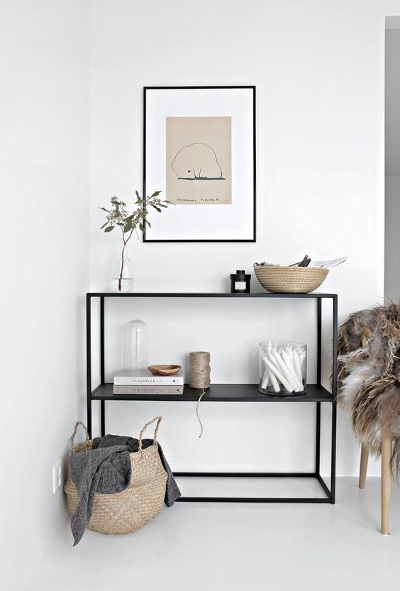 A console table can make a great stand-in for a proper entryway, if styled properly, like this minimalist black steel wire console table with black framed vintage line drawing on the wall above, small natural organic objects and art, a foldable basket with throw blanket inside, and a cozy gray fur throw blanket.