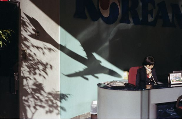 This image by Nick Turpin is a Street Scene taken in Piccadilly, London. This is a really clever image, the fact the building appears to be a travel agency, and there is the shadow of a plane pointing down to the lady at the desk is just very well put together context wise. The image works well due to the harsh quality of light which brings out crisp shadows so the plane can be identified as a plane.