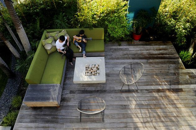 A custom couch is covered in bright green Sunbrella outdoor fabric. The deck can seat up to 12 people, and the concrete fire pit does double duty as a table.