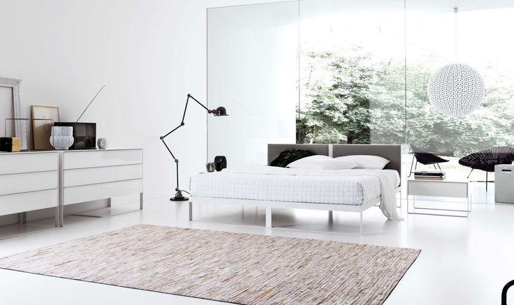 SHA ... Il letto abbina le linee pure e geometriche della struttura metallica con la morbidezza della testiera imbottita, sempre risolta con moderna essenzialità.  Il design abbinato al bianco, è di tuo gradimento?