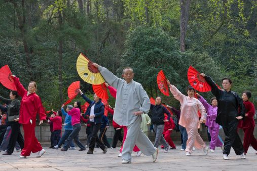 People practicing Taiji with fans in the park, Guiyang, Guizhou Province, China