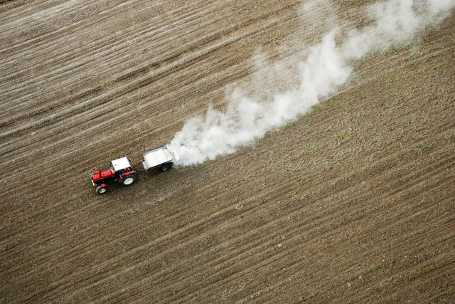 Ein Bauer düngt seinen Acker: Dabei gelangen Schwermetalle in den Boden.