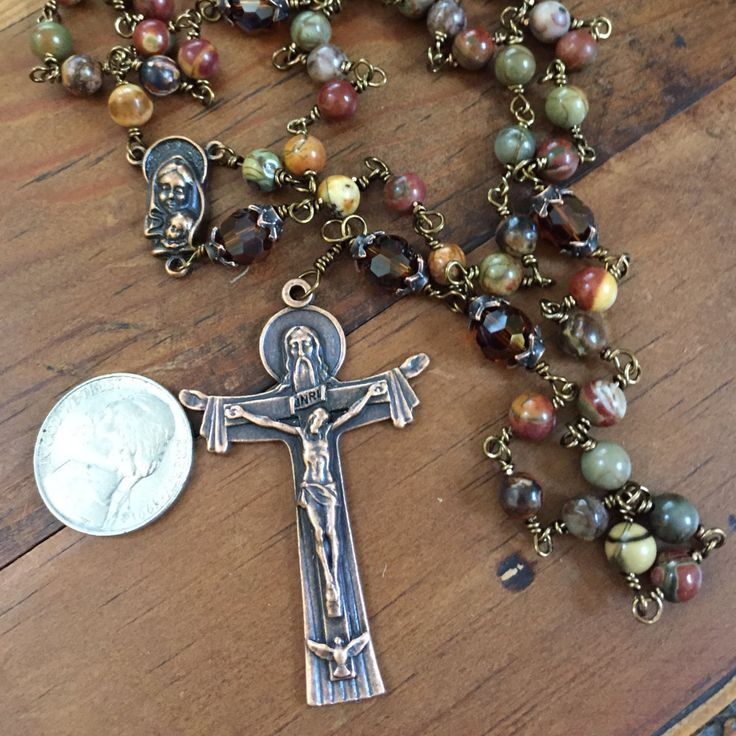 This rosary was made with jasper beads which are a semi-precious stone. The jasper beads were used for the Ave beads and the brown crystals as the Pater beads. The multi coloration of the jasper beads make this rosary appropriate for either a man or a woman. This rosary is very beautiful and was made to last. The rosary was wire wrapped by me and is very durable. The jasper beads have an earthy look to them and is great for people who do not like a lot of sparkle in their rosaries. The…