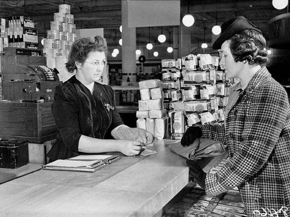 A woman using her ration book while shopping in an Eaton's department store, Toronto, Canada, 1940s.
