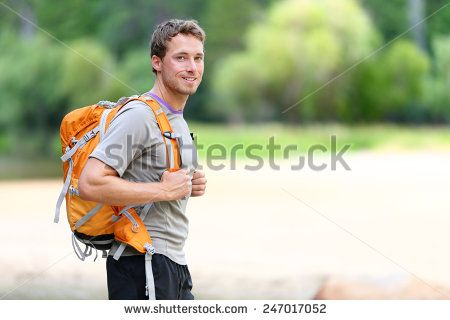 Hiking man portrait with backpack walking in nature. Caucasian man smiling happy…