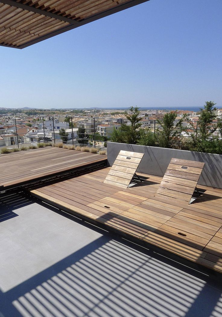 Seating area in rooftop terrace with built-in chaise longues. The chairs' back collapse and vanish inside the wooden platform.