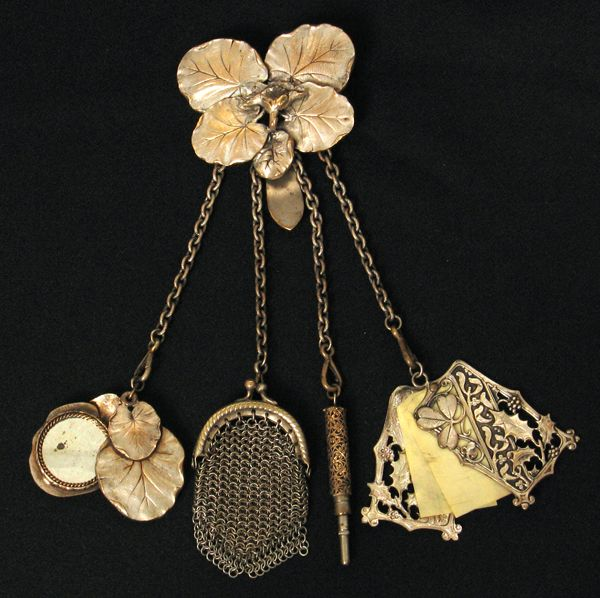 Elaborate Victorian silver-plate on brass lilypad chatelaine.  Includes a lilypad covered mirror, a small coin purse, a small retractable pencil, and a celluloid writing pad.