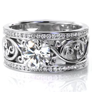 Design 3056 - Bold,  high polished filigree scroll work creates a open background for a beautiful 1.00 carat round cut diamond set in a four prong setting. Two rows of channel set diamonds are accented by a high polished finish creating a crisp border for the hand crafted filigree.